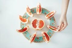 Рука ` s девушки принимая кусок грейпфрута от белой плиты От выше Питание здорового питания Стоковое Изображение RF