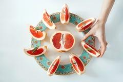 Рука ` s девушки принимая кусок грейпфрута от белой плиты От выше Питание здорового питания Стоковые Фотографии RF