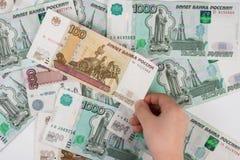 Рука ` s детей принимает деноминацию от кучи случайно разбрасываемых русских банкнот различной деноминации Стоковое Фото