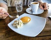 Рука ` s женщины держа вилку с укусом лимона кислая и свернутая сливк - установка кофейной чашки на таблице около плиты Стоковое Фото