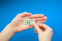 Рука ` s женщины держа малую банкноту 100 долларов США Стоковые Фотографии RF