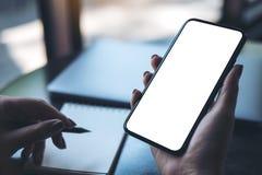 Рука ` s женщины держа черный мобильный телефон с пустым белым экраном настольного компьютера с компьтер-книжкой и тетрадью на та Стоковые Изображения