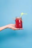 Рука ` s женщины держа smoothie клубники на голубой предпосылке Здоровая органическая концепция пить Люди на диете Стоковое Изображение