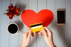 Рука ` s женщины держит кредитную карточку над таблицей, онлайн подарками покупок Стоковое Изображение RF
