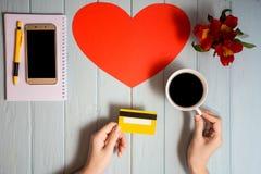 Рука ` s женщины держит кредитную карточку над таблицей, онлайн подарками покупок Стоковые Изображения