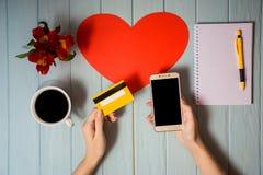 Рука ` s женщины держит кредитную карточку над таблицей, онлайн подарками покупок через телефон Стоковое Изображение