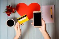 Рука ` s женщины держит кредитную карточку над таблицей, онлайн подарками покупок через телефон Стоковые Изображения