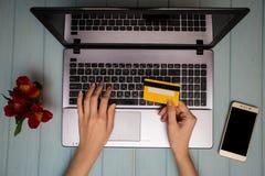 Рука ` s женщины держит кредитную карточку над таблицей, онлайн подарками покупок через телефон во время перерыва на чашку кофе Стоковое фото RF