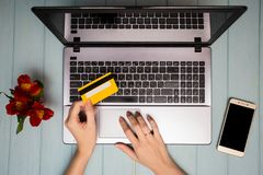 Рука ` s женщины держит кредитную карточку над таблицей, онлайн подарками покупок через телефон во время перерыва на чашку кофе Стоковое Изображение RF