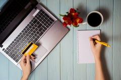 Рука ` s женщины держит кредитную карточку над таблицей, онлайн подарками покупок через телефон во время перерыва на чашку кофе Стоковое Изображение