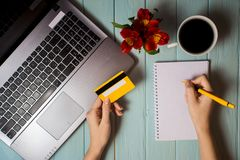 Рука ` s женщины держит кредитную карточку над таблицей, онлайн подарками покупок через телефон во время перерыва на чашку кофе Стоковые Изображения
