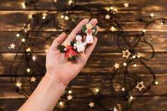 Рука ` s женщины держа деревянное рождество забавляется на предпосылке Стоковое Изображение