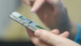 Рука ` s женщины держа серебряный мобильный телефон видеоматериал