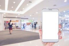 Рука ` s женщины держа умный телефон с backgroun супермаркета нерезкости Стоковая Фотография