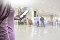 Рука ` s женщины держа умный телефон с backgroun супермаркета нерезкости Стоковое Изображение RF