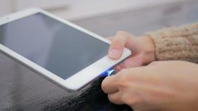 Рука ` s женщины затыкая черный зарядный кабель молнии в таблетку Стоковая Фотография