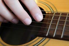 Рука ` s женщины играя гитару Стоковое Фото