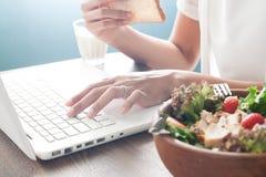 Рука ` s женщины используя портативный компьютер и еду отрезанного хлеба с Стоковое Изображение