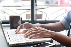 Рука ` s женщины используя портативный компьютер и мобильное устройство в кафе, дальше Стоковые Фотографии RF