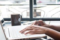 Рука ` s женщины используя портативный компьютер и мобильное устройство в кафе, Te Стоковое Изображение RF