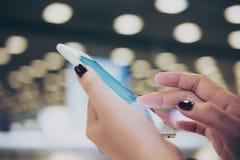 Рука ` s женщины касаясь и сползая пальцу на умном телефоне пока стоящ и ждущ заявка багажа стоковое изображение rf