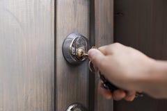 Рука ` s женщины кладет ключ в keyhole деревянной двери Se дома стоковые фотографии rf