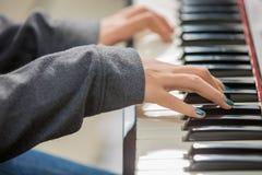 Рука ` s женщины крупного плана играя рояль Стоковые Изображения