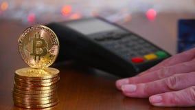 Рука ` s женщины оплачена карточкой банка используя стержень для оплаты на предпосылке золотых монеток bitcoins _ видеоматериал