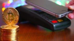 Рука ` s женщины оплачена карточкой банка используя стержень для оплаты на предпосылке золотых монеток bitcoins _ сток-видео