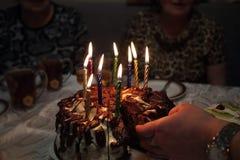 Рука ` s женщины принимая часть именниного пирога с свечами Стоковая Фотография