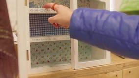 Рука ` s женщины раскрывает дверь меньшего кухонного шкафа акции видеоматериалы