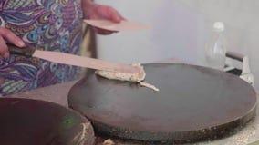 Рука ` s женщины с тернером поворачивает блинчик выпечки на другой стороне создателя блинчика сток-видео