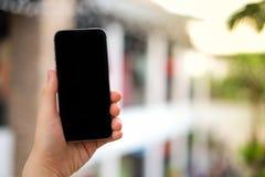 Рука ` s женщин используя экран черноты мобильного телефона для данных по поиска, стоковые изображения rf