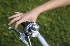 Рука ` s колеса и ребенка велосипеда на зеленой предпосылке стоковые фото