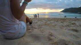 Рука ` s молодой женщины принимает чашку кофе Iced, делает глоточек и кладет ее назад на песок Заход солнца пляжа, Gopro видеоматериал