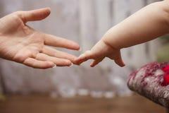 Рука ` s младенца достигая до своего Стоковые Фотографии RF