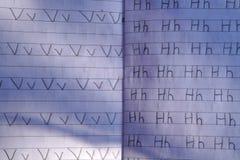 Рука ` s ребенка пишет в тетради с карандашем стоковое изображение