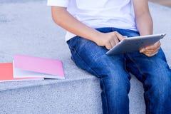 Рука ` s ребенка с планшетом и книгами конец вверх Стоковые Изображения