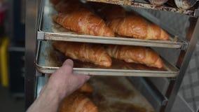 Рука ` s хлебопека принимает вне железный лист выпечки с свежими хлебобулочными изделиями сток-видео