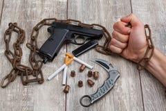 Рука ` s человека держа ржавую цепь, рядом с пистолетом, немного боеприпасы, нож и сигареты Стоковые Изображения RF