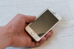 Рука ` s человека держит сломленный smartphone на светлой предпосылке стоковые изображения