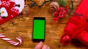 Рука ` s человека кладет телефон на таблицу, игрушки лежат на таблице и гирлянды горят Взгляд сверху сток-видео