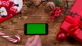 Рука ` s человека кладет телефон на таблицу, игрушки лежат на таблице и гирлянды горят Взгляд сверху акции видеоматериалы
