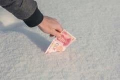 Рука ` s человека получает 100 китайцев RMB от снега Концепция Стоковая Фотография