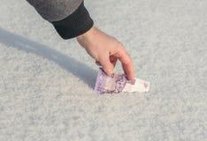 Рука ` s человека получает 10 рупий тысяч индонезийских от снега Стоковое Изображение RF