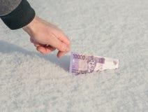 Рука ` s человека получает 10 рупий тысяч индонезийских от снега Стоковые Фотографии RF