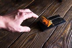 Рука ` s человека протягивает для банкноты которая приманка в мышеловке стоковые фотографии rf