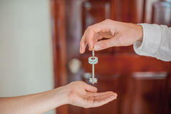 Рука ` s человека дает женщину ключа на предпосылке деревянной двери Дело с концепцией недвижимости Стоковые Фото