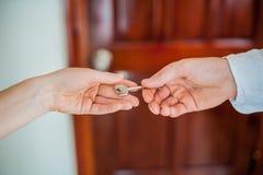 Рука ` s человека дает женщину ключа на предпосылке деревянной двери Дело с концепцией недвижимости Стоковые Фотографии RF