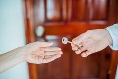 Рука ` s человека дает женщину ключа на предпосылке деревянной двери Дело с концепцией недвижимости Стоковые Изображения RF